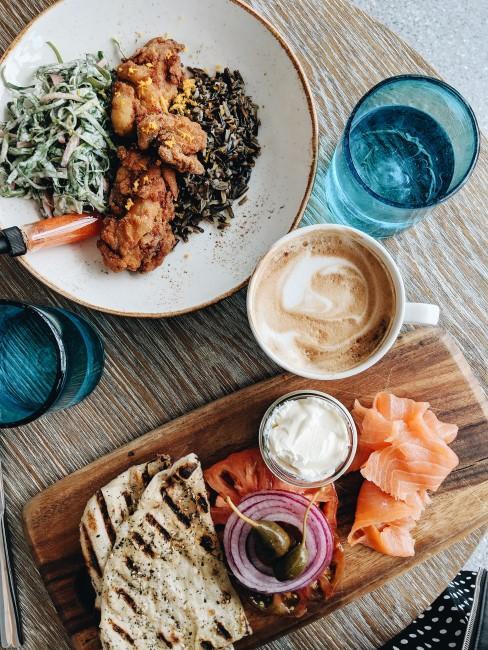 cafe, agua y una tabla de cortar con comida