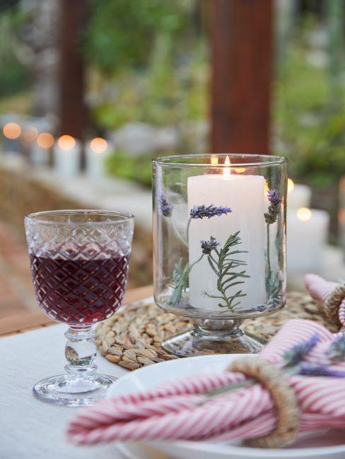 verre a vin rouge, structure a embossages decoratifs pose sur une table dressee et decoree avec un photophore transparent et une bougie blanche a l interieur, sous-verre en jute en