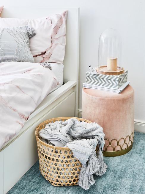 Lit avec panier à linge en osier et table de nuit en veours rose et détails or