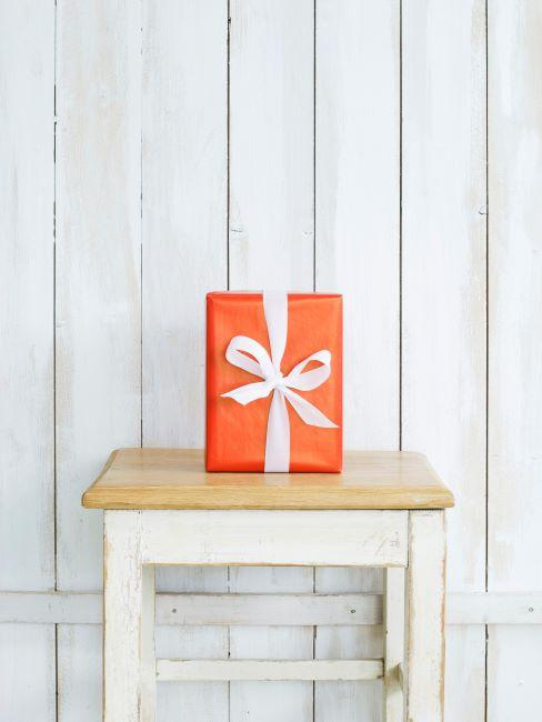 Cadeau dans un emballage orange sur tabouret rustique