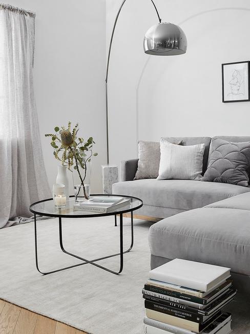 Coin salon avec canapé gris, tapis blanc et lampe en métal