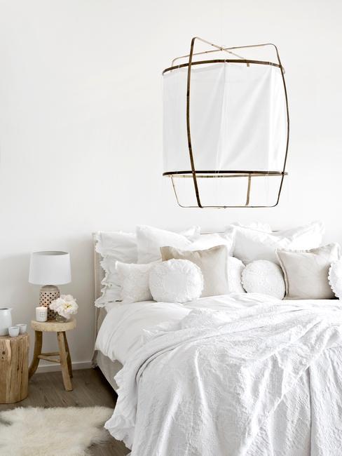 Lit blanc défait avec plusieurs coussins et un lampadaire blanc et or