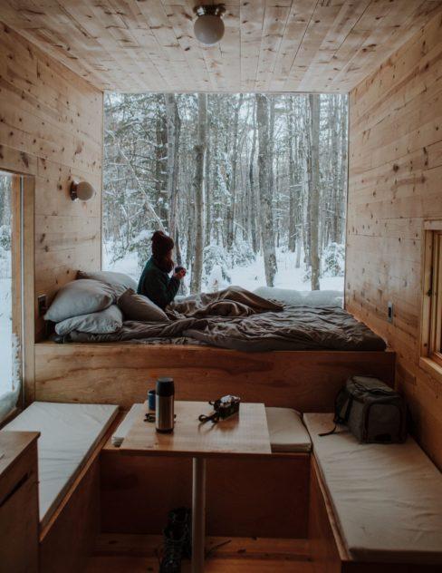 intérieur boisé d'un tiny house, une femme assise dans un lit en train de boire un café et regarder le bois enneigé à travers le grand vitre