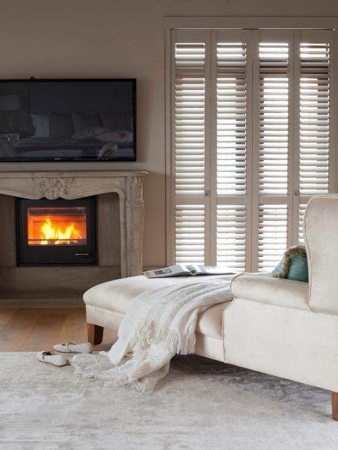 Intérieur avec cheminée, rideaux translucide et méridenne crème avec plaid posé dessus