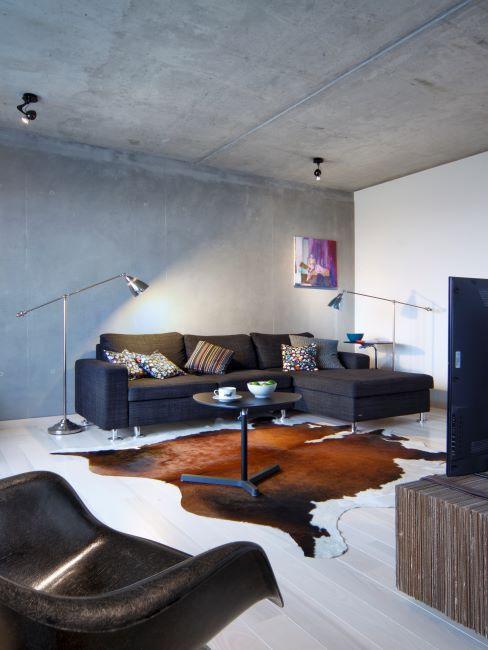 Salon avec murs bruts en beton, canape fonce et tapis peau de vache