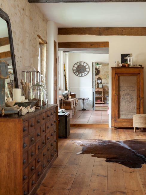 Couloir avec commode en bois vernis, tapis en peau de vache et miroir antique