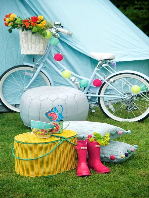 Jardin avec vélo bleu, guirlande multicolore, coussins à pompons et table basse en osier jaune