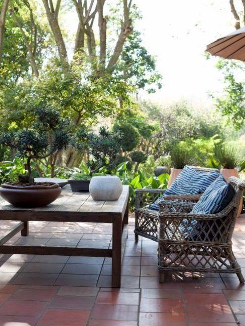 Terrasse avec salon de jardin en bois et avec carrelage en pierres rouge