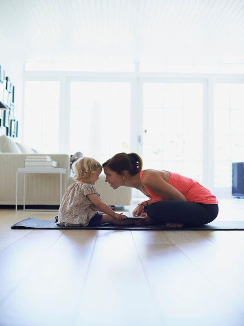 Femme avec son enfant sur un tapis de yoga dans le salon