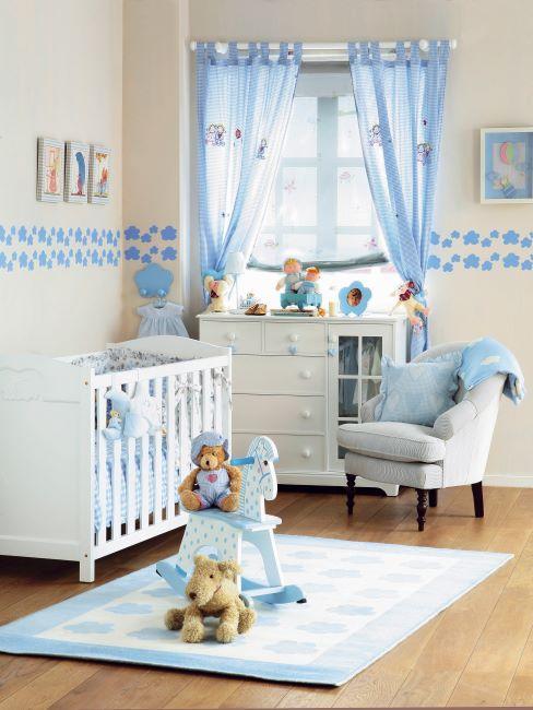 Chambre blanche et bleue de nouveau né avec rideaux bleus et jouets