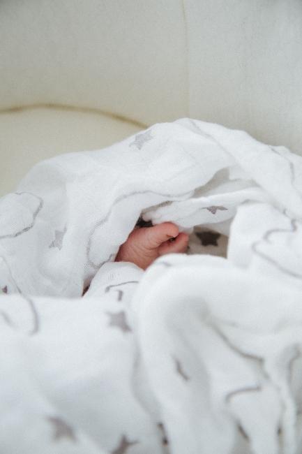 Petit pied de bébé dans draps de lit blancs
