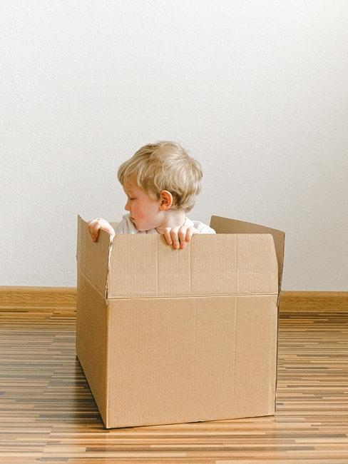 Petit garçon assis dans un carton