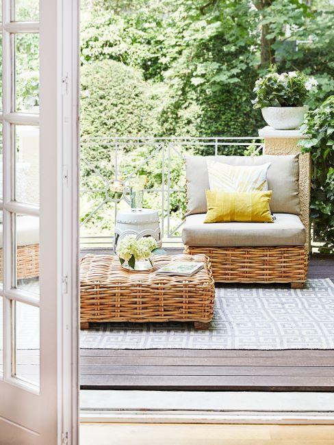 terrasse avec sol en bois avec tapis et mobilier en rotin