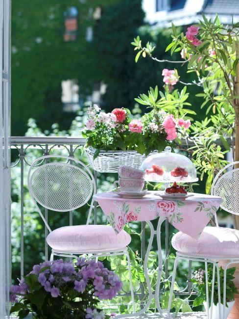 Balcon style romantique avec mobilier en fer blanc et fleurs en jardinière