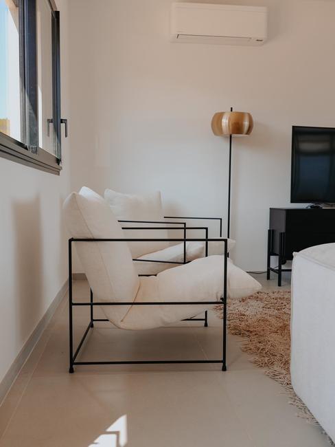 Fauteuil blanc avec armature noir dans un salon blanc, lampadaire doré