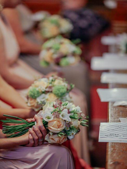 Invites de mariage assis avec des bouquets de fleurs lors de la ceremonie