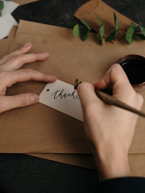 Personne écrivant ses remerciement sur papier recyclable