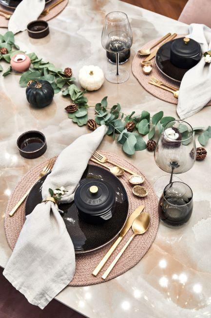 table de noel avec serviettes blanc creme, assiettes noir, couverts dores et decoration florale