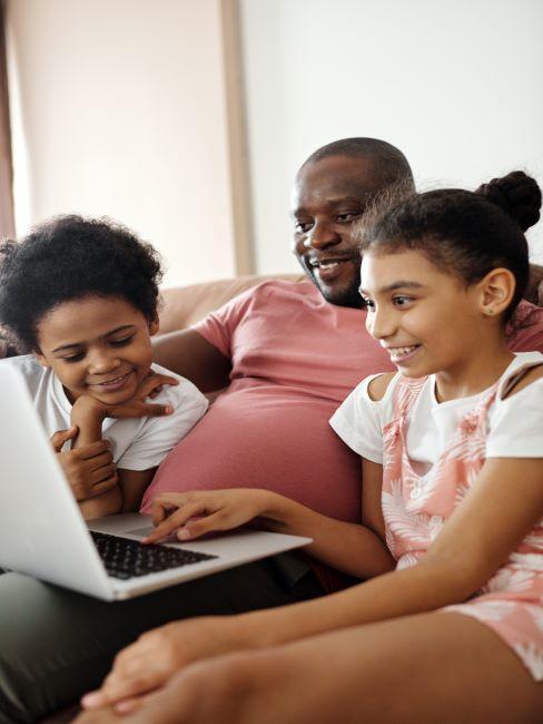 un pere regarde un ordinateur portable avec ses deux enfants