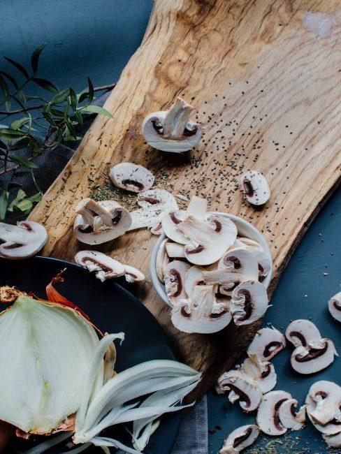 planche en bois avec oignon et champignons decoupes