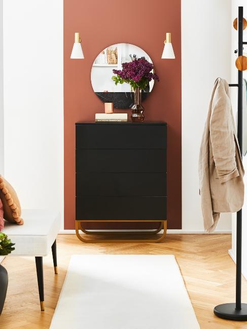 couloir avec meuble en bois foncé et miroir rond