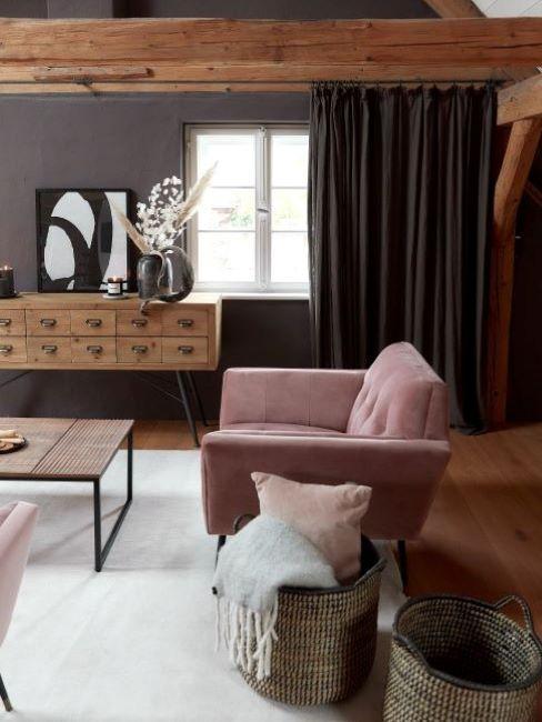 soggiorno con travi a vista in legno, consolle e parete sui toni del marrone e poltrona rosa