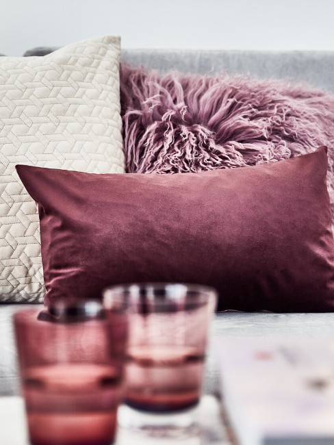 Cuscini bordeaux su divano grigio