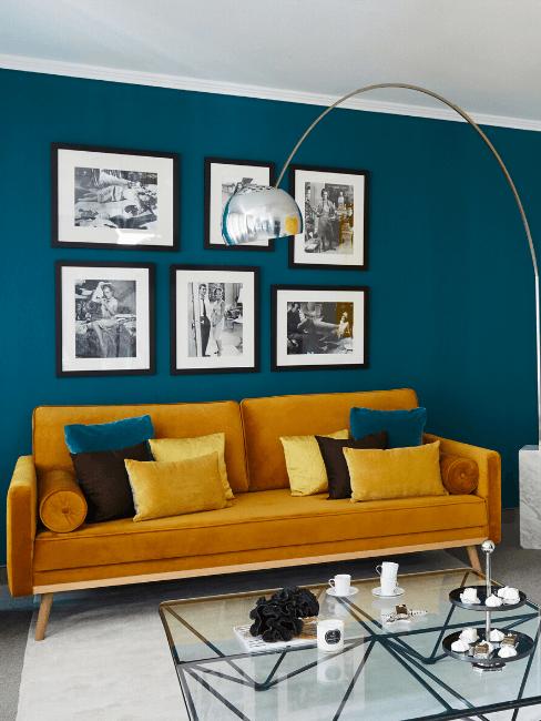 Quadri appesi su parete blu e divano giallo