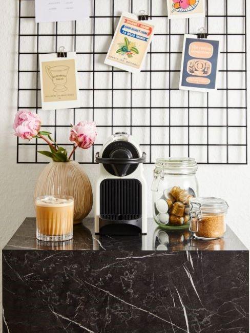 piano cucina in marmo nero con macchina del caffè e cialde