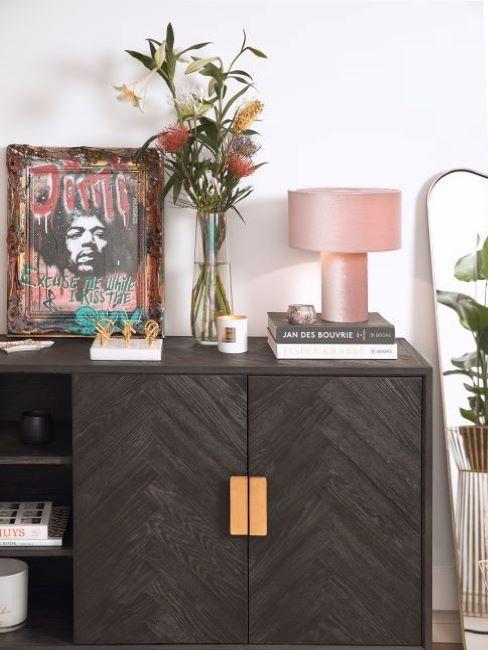 consolle in legno scuro con vaso di fiori e oggetti decorativi