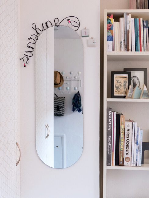 Specchio appeso con libreria