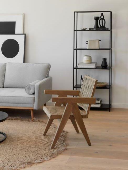 soggiorno con divano grigio, poltrona in vimini e libreria a parete