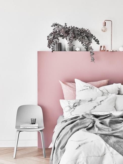 Beddengoed op bed naast een grijze stoel