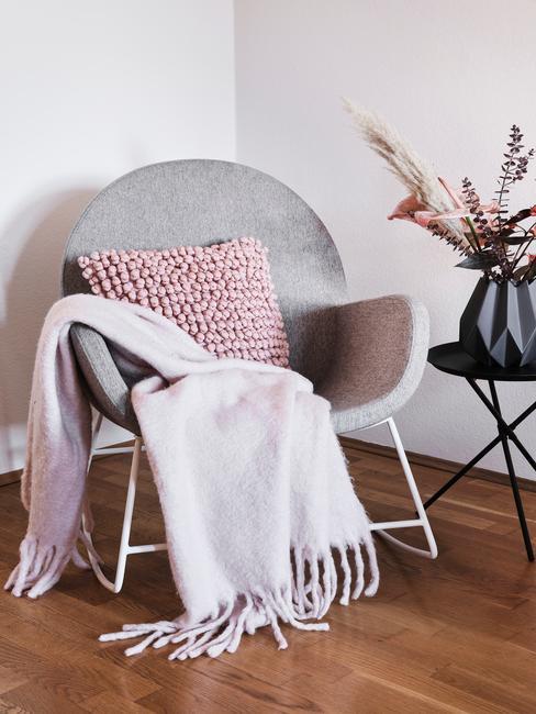 Zachte plaid op fauteuil met roze sierkussen