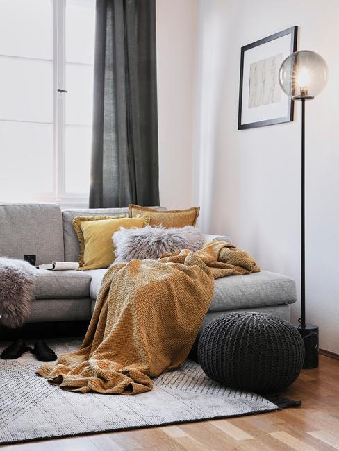 Gele plaid van alpaca wol op grijze zitbank met gele en grijze sierkussens naast een vloerlamp