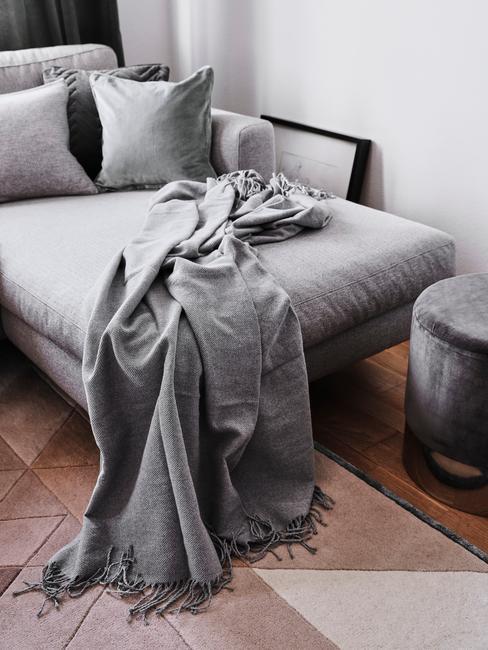 Zachte grijze plaid op grijze zitbank met sierkussens