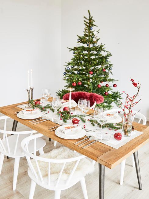 Houten tafel met wit serviesgoed en zilveren bestek, hoge kandelaars en sparren takken als decoratie naast de kerstboom