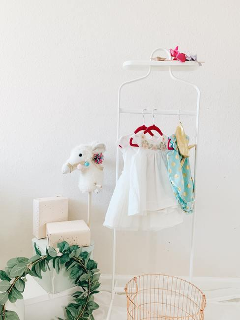 Babykamer meisje: kleding voor meisjes hing aan een hanger in een lichte kamer in een moderne stijl