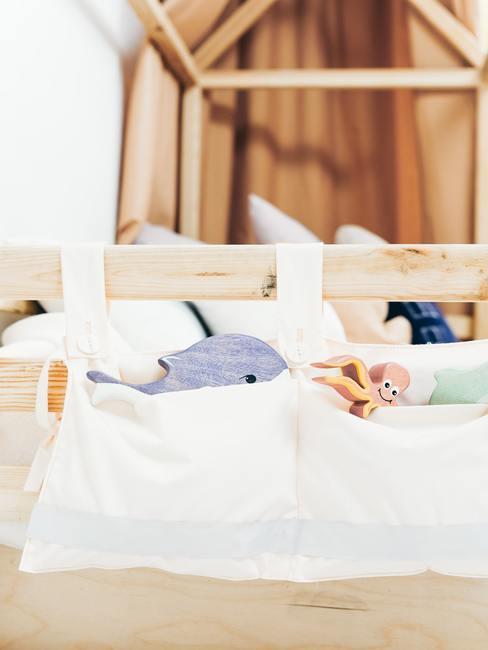 Babybedje met wit linnen en een ophangzakje met knuffels