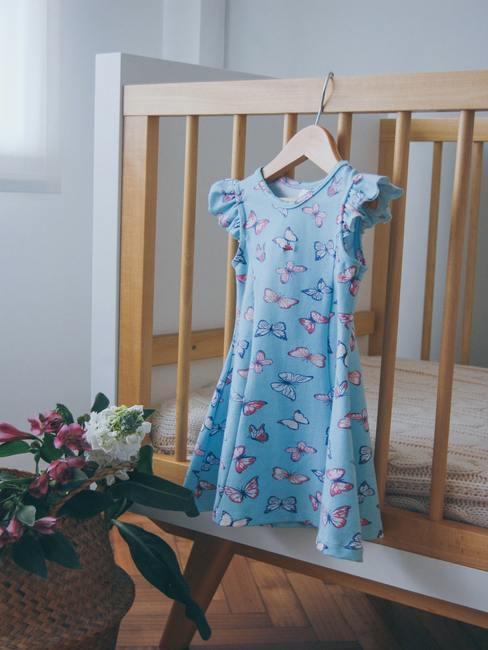 Babykamer meisje:blauwe jurk hing aan het frame van een houten wieg