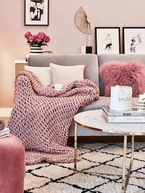 Een grijze bank met sierkussens en zachte chunky knit plaid naast een marmeren salontafel met koffietafelboeken