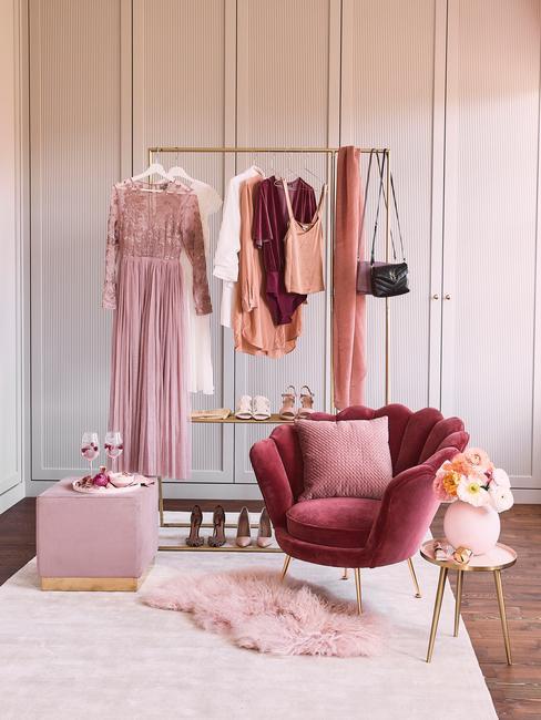 Een gouden kleerhanger naast een roze fauteuil met een sierkussen en roze bijzettafel