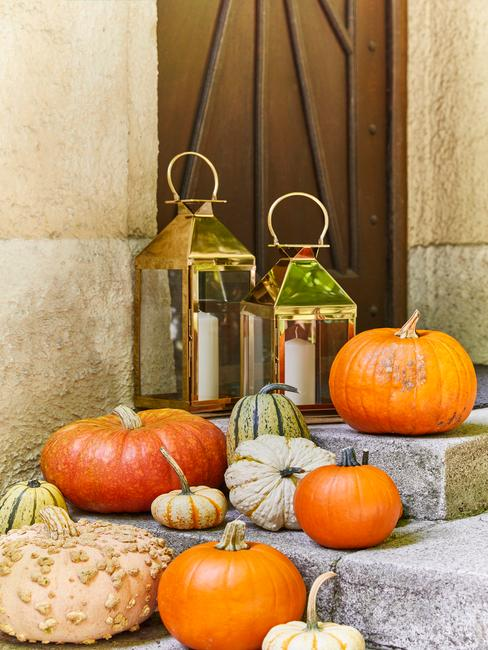 Herfst decoratie echte oranje pompoenen op trap voor voordeur