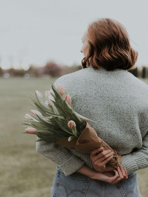 bloemen achter de rug van een vrouw