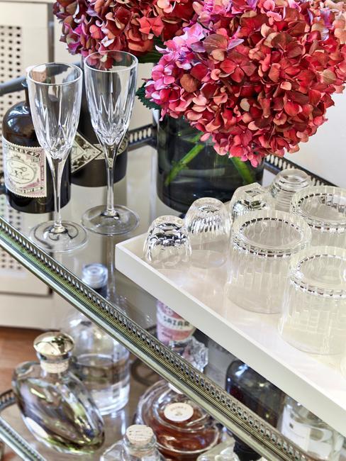 Roze bloemen in vaas en glazen en drank op bar cart
