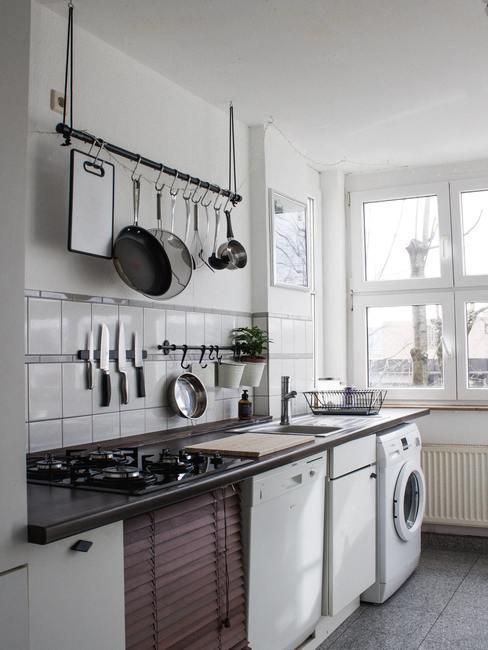 keuken met pannen, gasfornuis, wastafel en wasmachine