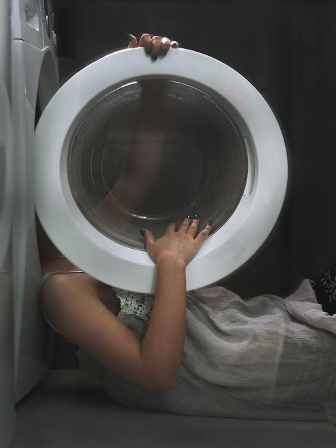 persoon die wasmachine opent : Wasmachine schoonmaken