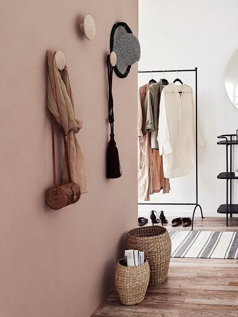 Beige muur met wandhaken en kledingstang