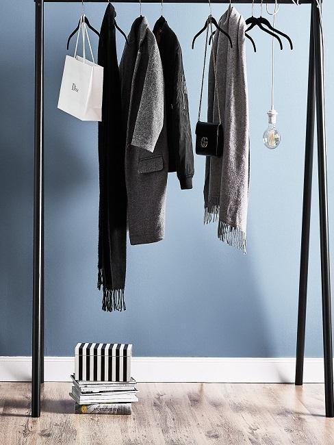 Grijse kleeren en Tas op zwarte kledingstang voor blauwe muur