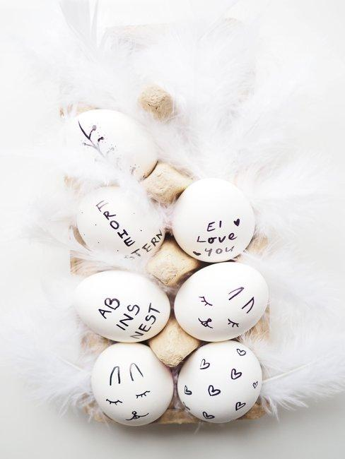 Witte eieren met veren in eierdoos